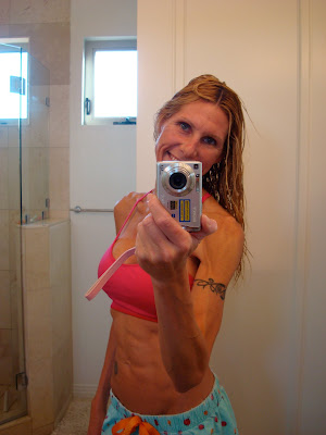 Woman showing abs and smiling in mirror