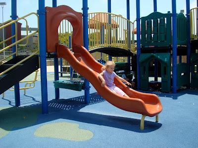 Young girl sliding down slide