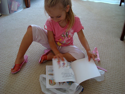 Young girl looking at book on floor