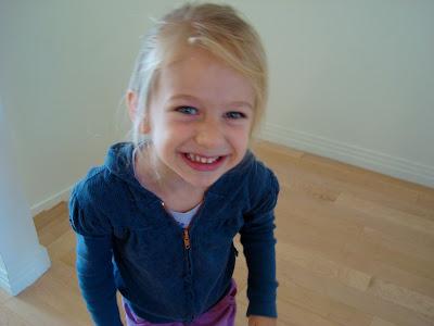 Young girl smiling in blue zip up sweatshirt