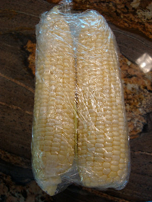 Two ears of corn wrapped in plastic wrap