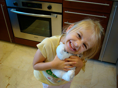 Little girl in kitchen hugging toy