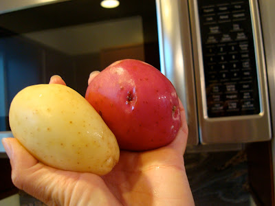 Two potatoes going into microwave