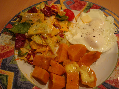 Eggs, sweet potatoes with salad on plate