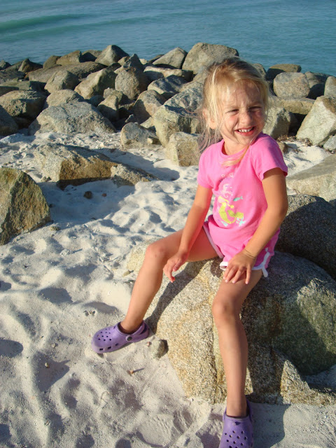Young girl sitting on rocks on beach