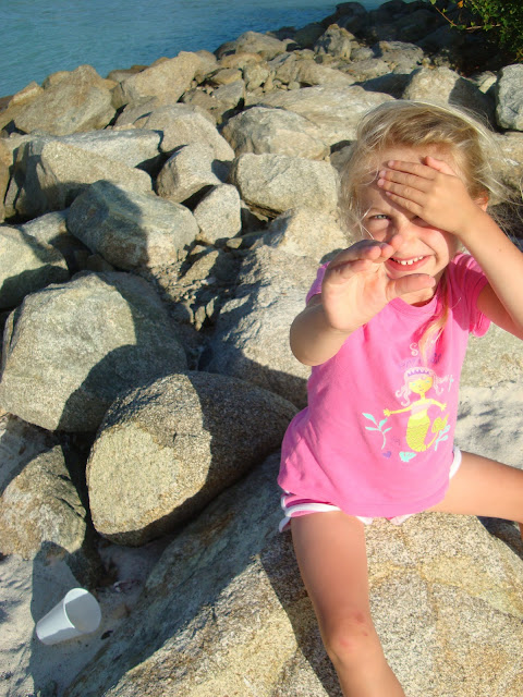 Young girl on rock shielding eyes from sun and reaching out
