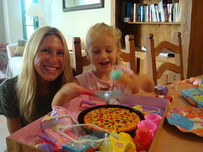 Woman and young girl at table playing with gifts
