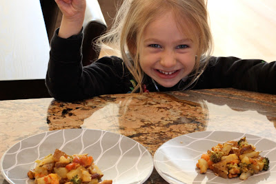Young girl smiling in front of plates of Cheezy Vegetable Bake
