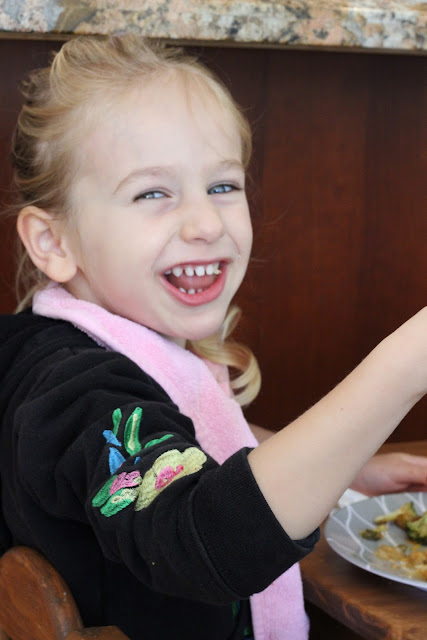 Young girl smiling while eating
