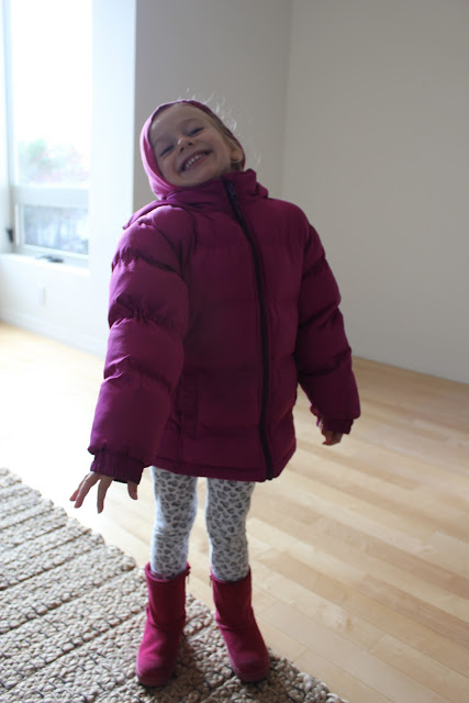 Young girl standing in puffer jacket and boots