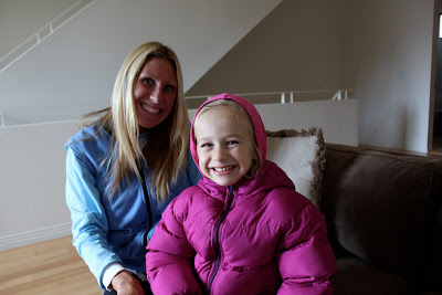 Young girl and woman on couch bundled up smiling