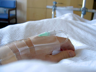 hand with an iv drip resting on a hospital bed