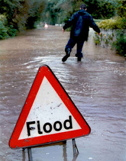 man wading through floods