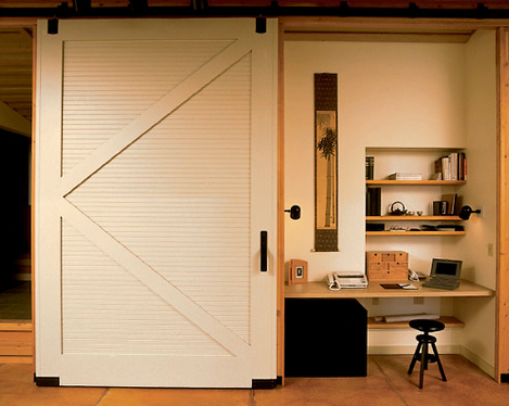 Interior sliding door hides closet office content in a for Barn doors for home office