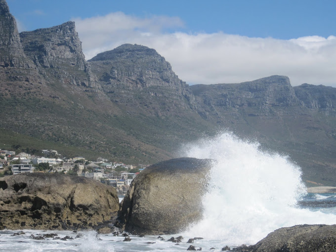 Waves crashing at Camps Bay with Table Mountain and the 12 apostles behind