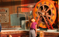 An imaginary idea factory--a girl looks at a big gear.