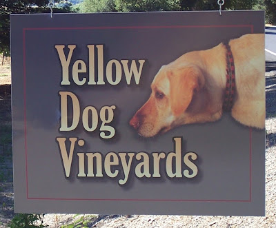 sign hanging from a post that says Yellow Dog Winery, with a painted picture of a yellow dog thrusting his head toward the word dog