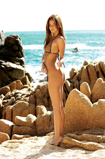 Miranda Kerr on beach lying on sand