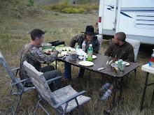 Guys eating at camp