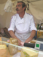 Frenchman with classic moustache selling cheese