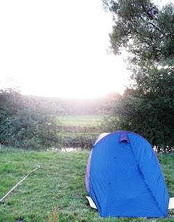 Tent on riverbank with sun setting