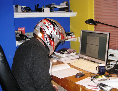 Mr A reading at his desk wearing a full face crash helmet