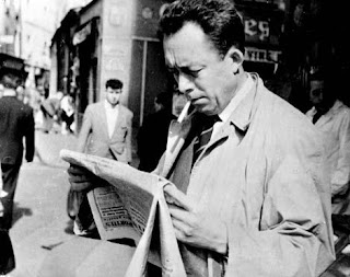 Albert Camus reading a newspaper