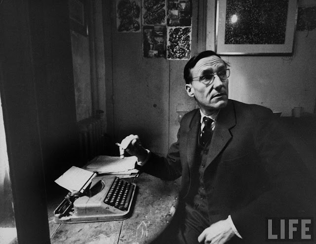 Author William S. Burroughs sitting at a crude table with typewriter, holding a cigarette and looking away. Photograph by Loomis Dean. Life Magazine