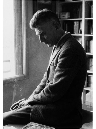 Samuel Beckett sitting on his desk