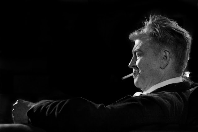 David Lynch sitting back on a chair