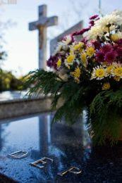 Fotografía de unas flores sobre una lápida en primer plano con la vista de una cruz al fondo