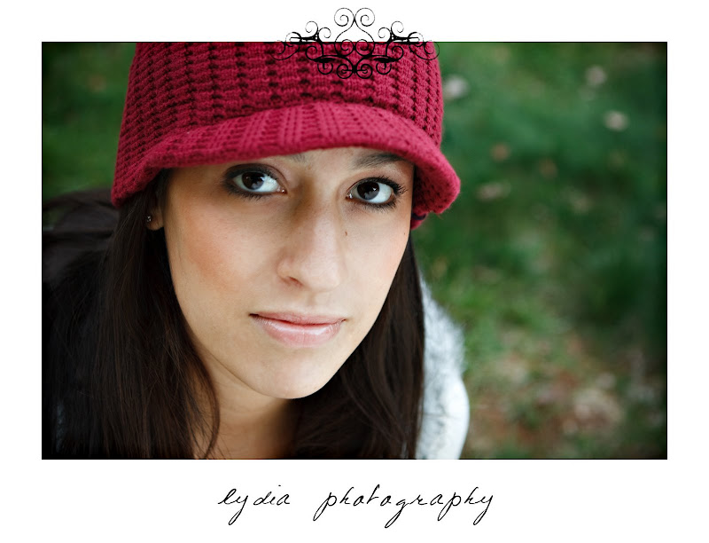 Bride looking serious with a red hat on at lifestyle engagement portraits in Grass Valley, California