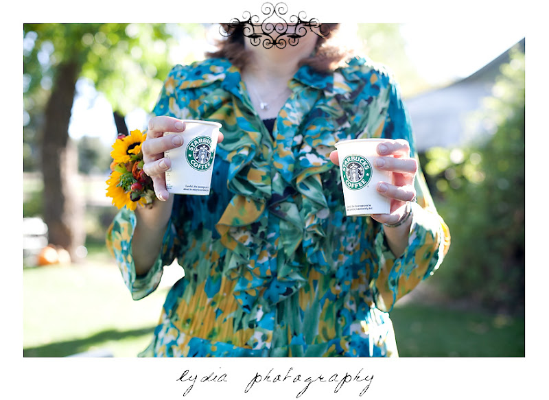 Mother of the groom holding cups of Starbucks coffee at a Kenwood Farms & Gardens wedding