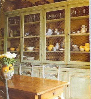 This dining room is so warm with the pale green hutch and the farm
