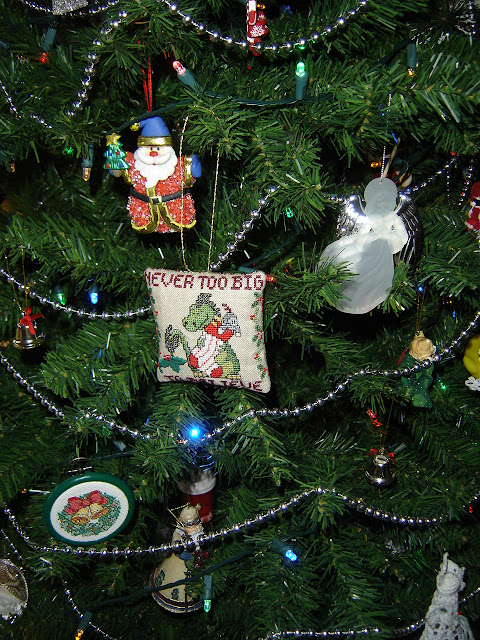 A hand stitched Christmas decoration of a dragon holding a Christmas stocking, which says Never Too Big To Believe