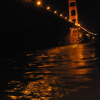 Sailing under the Golden Gate Bridge on a calm, clear night with a full moon