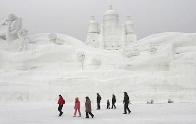 Visitors walk past a snow sculpture.