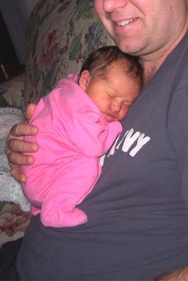 Νεογέννητο μωρό στην αγκαλιά του μπαμπά του με τα ποδαράκια σα βατραχάκι