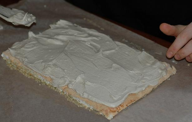 Spreading the wattleseed cream on the meringue base