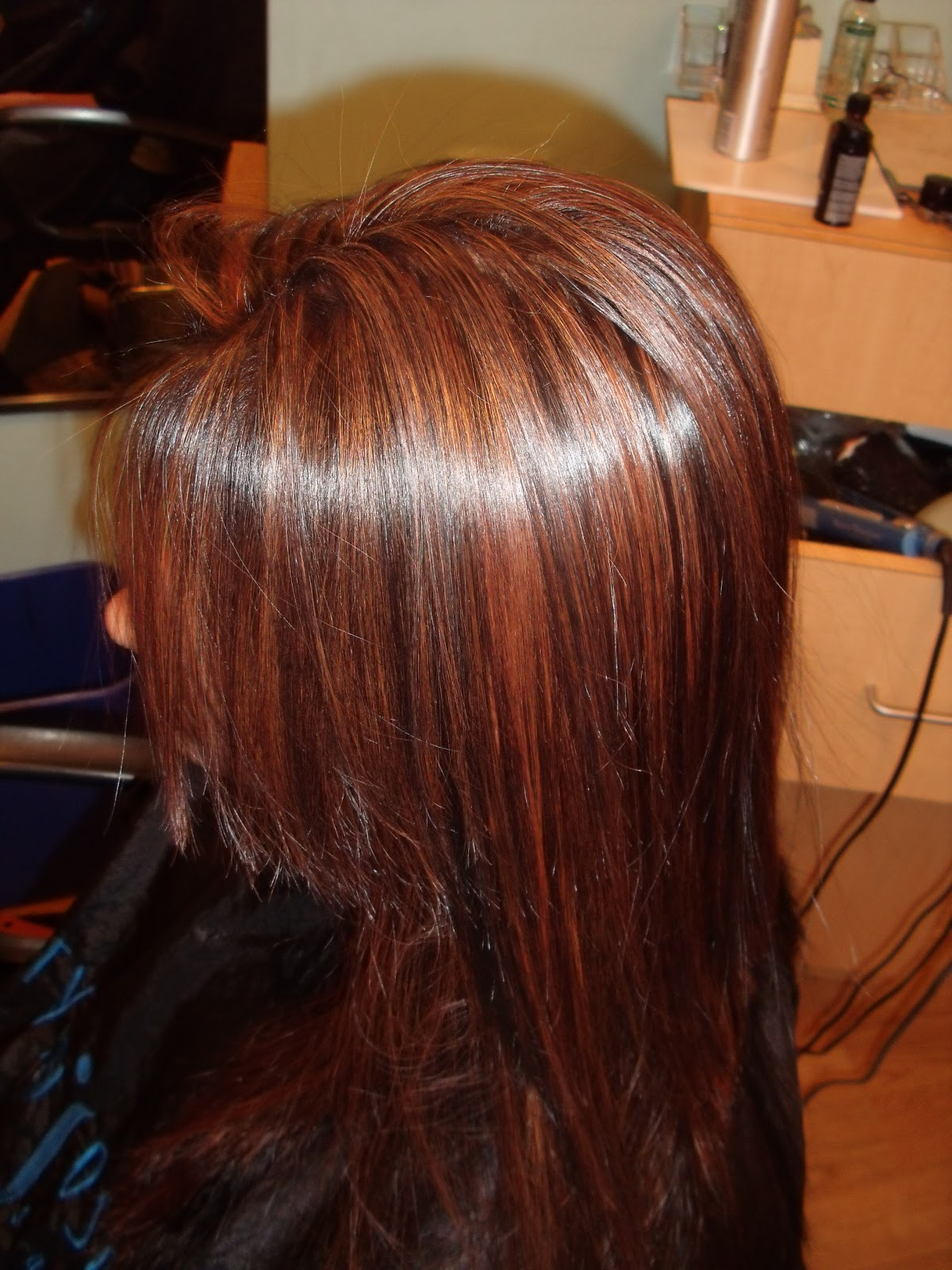 "Highlights toned with Redken ""cherry cola"" color"