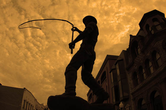 The Bullwhacker statue in downtown Helena, Montana under a forest fire hazed sunset.