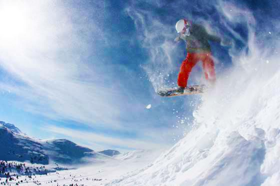 A snowboarder jumping off a cornice through blowing snow at Copper Mountain, Colorado.