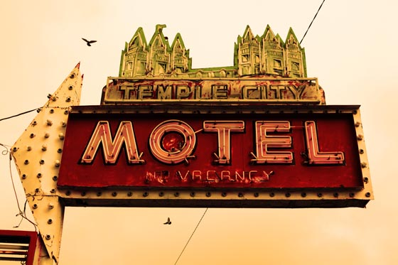 Birds flying above the old neon sign at the Temple City Motel near downtown Salt Lake City, Utah.