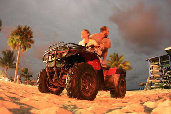 A couple sneaking away on a beach ATV in the middle of the night on Grand Bahama Island at the Wyndham Fortuna Resort.