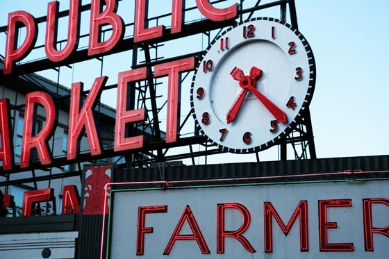 The clock and neon signs at the Pike Place market in Seattle.