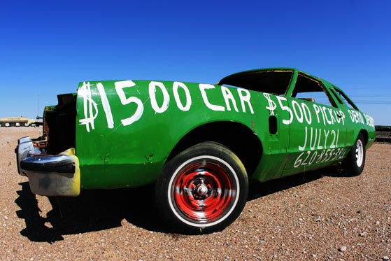 A long, green demolition derby car parked off the highway somewhere in Kansas.