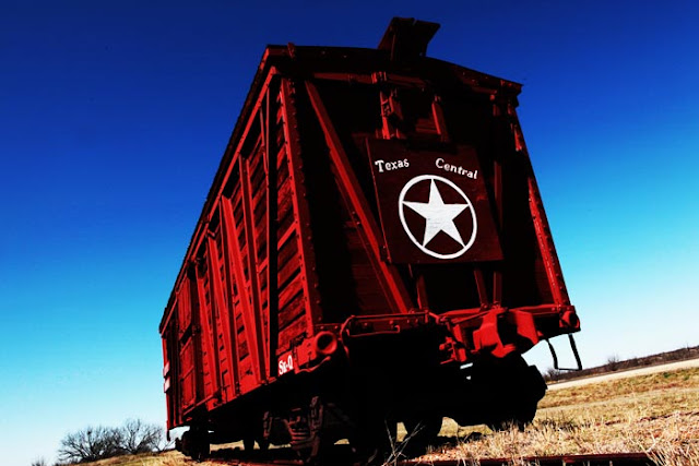 An old Texas train car with a 'Texas Central' logo on the back.