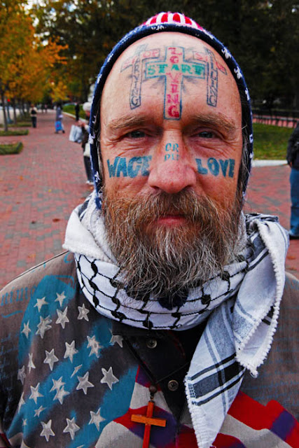 A man named Start Loving with numerous face tattoos protesting outside the gates at the White House in Washington D.C.