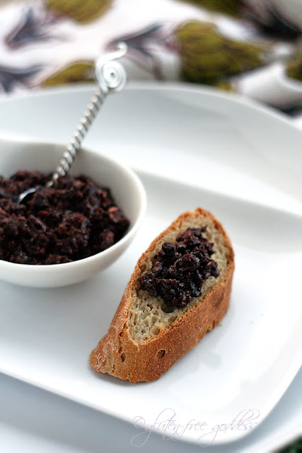 Olive tapenade spread on a slice of gluten free baguette