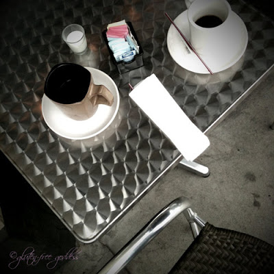 iPhone photo of a street cafe table with coffee cups and Splenda packets